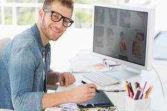 Handsome editor working with digitizer smiling at camera Royalty Free Stock Photography