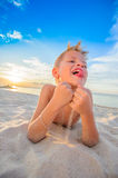 Handsome eight years boy on beach performs acrobatic sketches an. Handsome eight years boy on beach playing with a stream of sand. Thailand, Koh Samui, Ban Tai Royalty Free Stock Image