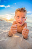 Handsome eight years boy on beach performs acrobatic sketches an. Handsome eight years boy on beach playing with a stream of sand. Thailand, Koh Samui, Ban Tai Royalty Free Stock Photo