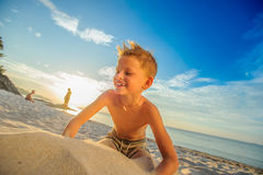 Handsome eight years boy on beach performs acrobatic sketches an. Handsome eight years boy on beach playing with a stream of sand Royalty Free Stock Photos