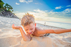 Handsome eight years boy on beach performs acrobatic sketches an. Handsome eight years boy on beach playing with a stream of sand Royalty Free Stock Images