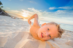 Handsome eight years boy on beach performs acrobatic sketches an. Handsome eight years boy on beach playing with a stream of sand Royalty Free Stock Photo