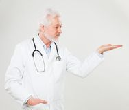 Handsome elderly doctor holds something Royalty Free Stock Images