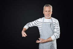 Handsome elderly male person holding fictitious pan. Love cook. Attractive smiling man wearing striped apron while standing against black background keeping Royalty Free Stock Images