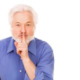 Handsome elderly man asks to silence. With finger on lips isolated over white background royalty free stock image