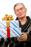 Handsome elderly man holding gift boxes Stock Image