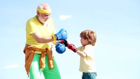 Handsome elderly man practicing boxing kicks. Healthy fighter Grandfather and grandson with boxing gloves. Grandfather. And grandson doing boxing training in stock footage