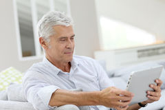 Handsome elderly man using tablet. Senior man relaxing in sofa and using digital tablet Royalty Free Stock Photo
