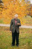 A handsome elderly man wearing glasses is using a phone. Walk in the park in autumn Stock Photo