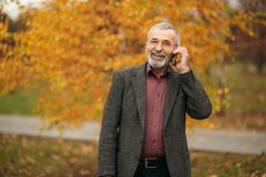 A handsome elderly man wearing glasses is using a phone. Walk in the park in autumn Stock Image