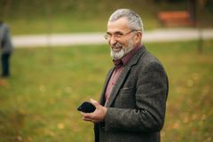 A handsome elderly man wearing glasses is using a phone. Walk in the park in autumn Royalty Free Stock Photo