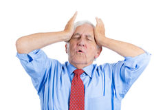 Handsome elderly man with white hair in blue shirt and red tie, stressed and frustrated with raging headache i Royalty Free Stock Photos