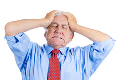 Handsome elderly man with white hair in blue shirt and red tie, stressed and frustrated with raging headache stock image