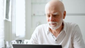 Handsome elderly senior man working on laptop computer at home. Remote freelance work on retirement. Handsome elderly senior man working on laptop computer at stock video