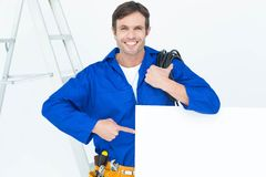 Handsome electrician with wire pointing at bill board Royalty Free Stock Photos