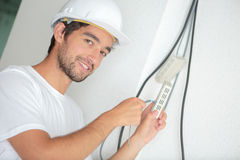 Handsome electrician wiring to wall at construction site Royalty Free Stock Image