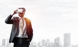 Handsome elegant businessman experiencing impressive virtual reality and business city at backdrop stock images