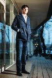 Handsome elegant fashion young man in coat on street outdoors evening stock photo