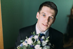 Handsome elegant groom in black suit with a wedding bouquet close-up.  Royalty Free Stock Images