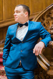 Handsome elegant groom posing looking towards on old wooden stairs at the background of luxury interior Royalty Free Stock Image