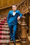 Handsome elegant groom posing on old wooden stairs at the background of luxury interior Stock Photo