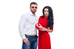 Handsome elegant guy is presenting a heart shaped gift to his beautiful girlfriend and smiling, valentines day theme. Isolated on white background royalty free stock photography