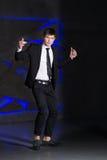 Handsome elegant man in black suit. Success, smile on blue lights background Stock Photo