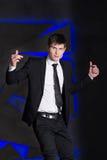 Handsome elegant man in black suit. Success, smile on blue lights background Royalty Free Stock Photos