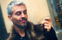 Handsome elegant man with pocket watch and wolf fur.  Royalty Free Stock Image