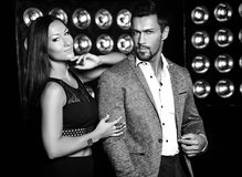 Handsome  elegant man in suit with beautiful sexy woman posing on black studio lights background. Fashion photo of handsome  elegant men in suit with beautiful Stock Photography