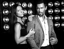 Handsome  elegant man in suit with beautiful sexy woman posing on black studio lights background. Fashion photo of handsome  elegant men in suit with beautiful Stock Photos