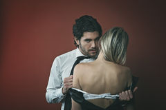 Handsome elegant man undressing woman Stock Photo
