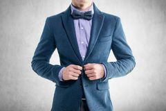 Handsome elegant young fashion man in coat tuxedo. Classical suit and bow tie Royalty Free Stock Photos
