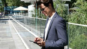 Young business man using tablet PC outdoor. Handsome eleganty young business man using tablet computer, with animated transparent code appearing next to him stock footage