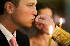 Handsome emotional groom kissing wedding ring holding candle in Stock Photography