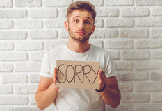 Handsome emotional guy. Handsome guy in casual clothes is holding a cardboard tablet with word 'sorry' and looking at camera, on white brick wall background Royalty Free Stock Photo