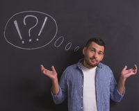 Handsome emotional man. Handsome confused young man is lifting his hands in dismay and looking at camera, standing against blackboard with drawn speech bubble royalty free stock photos