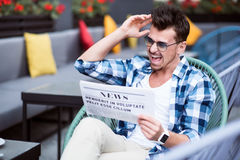 Handsome emotional man reading newspaper Royalty Free Stock Photo