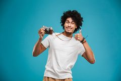 Handsome emotional young african curly man. Picture of handsome emotional young african curly man photographer isolated over blue wall background holding camera Stock Photos