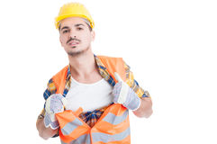 Handsome engineer acting like a super hero in his workwear. While holding his shirt and vest isolated on white background Stock Photo
