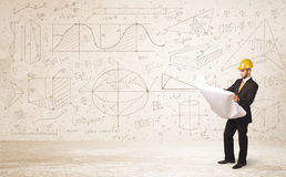Handsome engineer calculating with hand drawn background Stock Photos