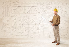 Handsome engineer calculating with hand drawn background Royalty Free Stock Images