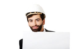 Handsome engineer in helmet holding empty banner. Royalty Free Stock Images