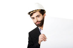 Handsome engineer in helmet holding empty banner. Royalty Free Stock Photos