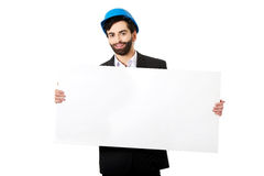Handsome engineer in helmet holding empty banner. Stock Photo