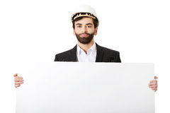 Handsome engineer in helmet holding empty banner. Royalty Free Stock Photo