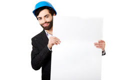 Handsome engineer in helmet holding empty banner. Stock Photos