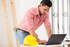 Handsome engineer at work. Attractive young engineer doing some construction work and using a laptop on site Stock Photography