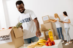 Handsome enthusiastic man helping as a volunteer. With an open heart. Devoted altruistic energetic guy working in charity foundation pro bono and helping people Royalty Free Stock Photo