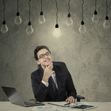 Handsome entrepreneur looking lightbulb Royalty Free Stock Photography